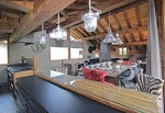 Looking across the kitchen and into the living area, industrial looking lights hang from the exposed wooden beams