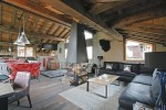 The living area of a ski chalet in Courcheval, fire burning in the centre of the room, bulls head on the wall