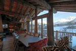 The dining area of a ski chalet in Courcheval, with a view of the sun setting over the mountains, visible through the windows