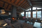 The living area of a ski chalet in Courcheval, with a roaring fire in middle of room and mountains visible through the windows