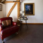 Newly furnished and designed barn in Kent depicting a red leather arm chair in front of exposed wooden beams